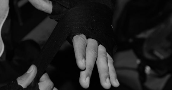 Top 10 hand wraps for boxing - featured image of a boxers hand wrapping their wrists and knuckles.