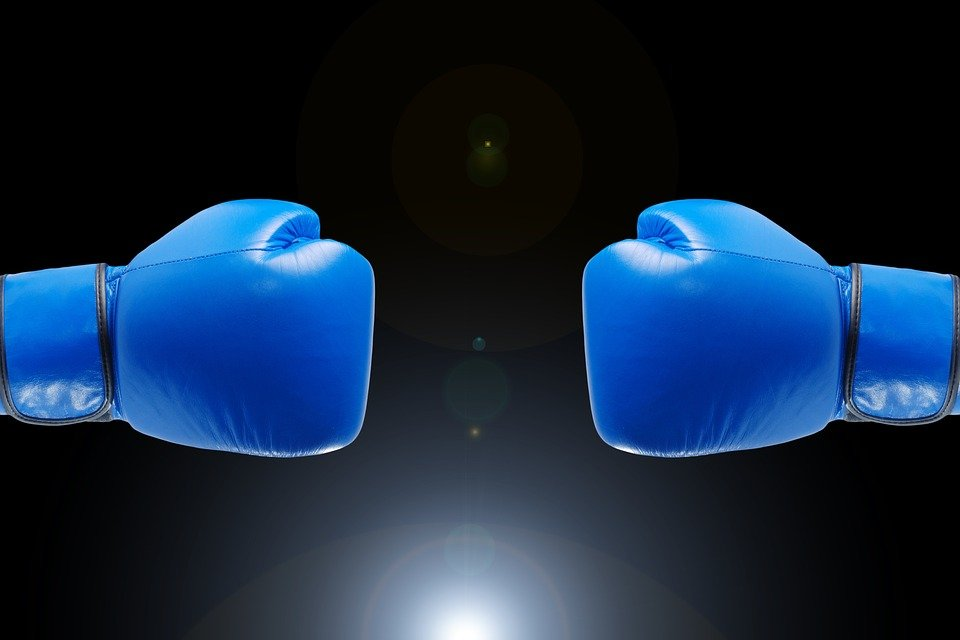 Best Junior Boxing Gloves Reviewed and Rated - Featured image of 2 blue boxing gloves on a dark black background.