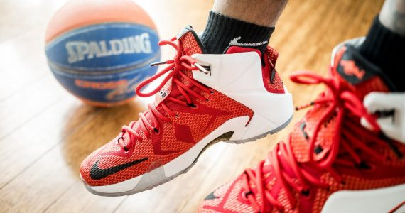 Best basketball shoes for ankle support featured image. Basketball shoes dangling by a hard surface court and ball.